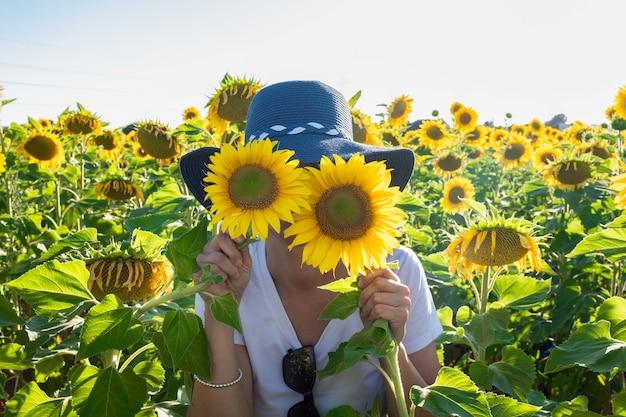 Donna con cappello che gioca con due piante di girasoli