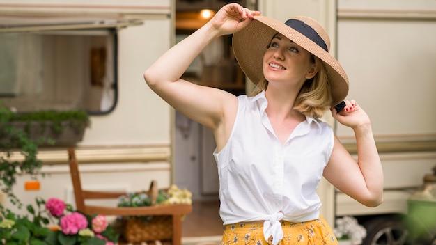 Donna con cappello che gode di un viaggio con una roulotte