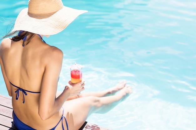 Donna con cappello con cocktail seduto sul bordo piscine