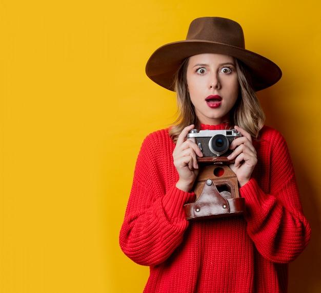 Donna con cappello con macchina fotografica d'epoca