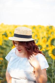Donna con cappello di paglia e vestito di girasoli.