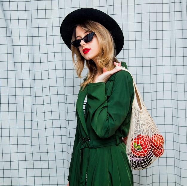 Donna con cappello e mantello verde in stile anni '90 con borsa a rete