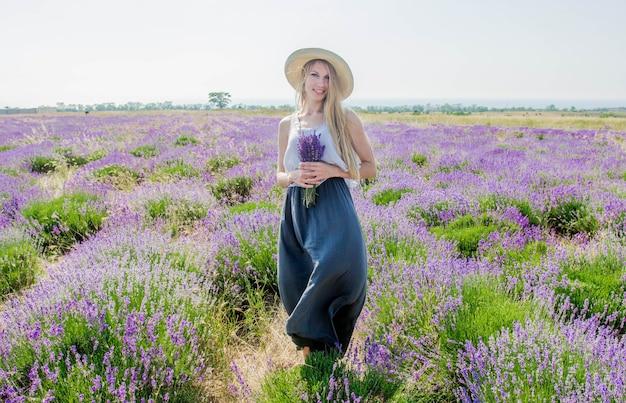 Donna con cappello e vestito sul campo di lavanda
