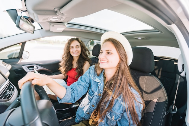 Donna con cappello guida auto