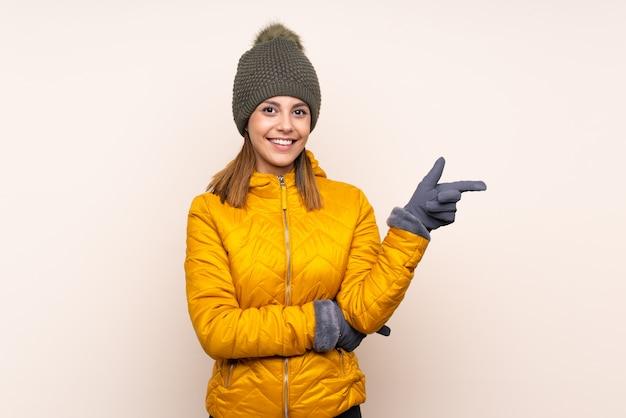 Donna con cappello invernale su muro isolato che punta il dito verso il lato