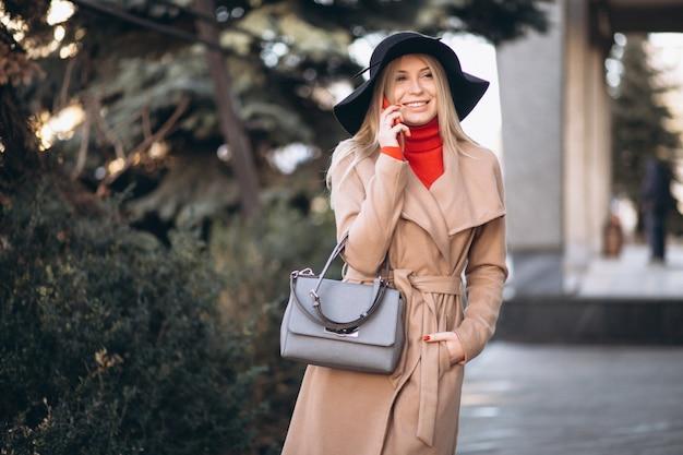 Donna con cappello nero parlando al telefono in strada