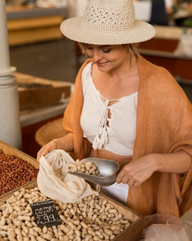 Donna con cappello prendendo cibo essiccato al mercato
