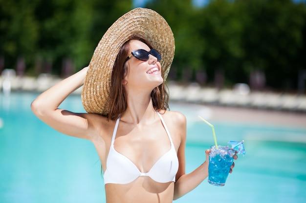 Donna con cappello rilassante in piscina con cocktail