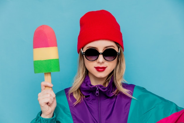 Donna con cappello rosso, occhiali da sole e tuta degli anni '90 con gelato giocattolo