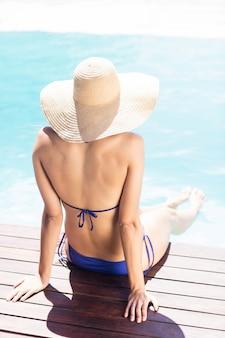 Donna con cappello seduto sul bordo piscine in una giornata di sole