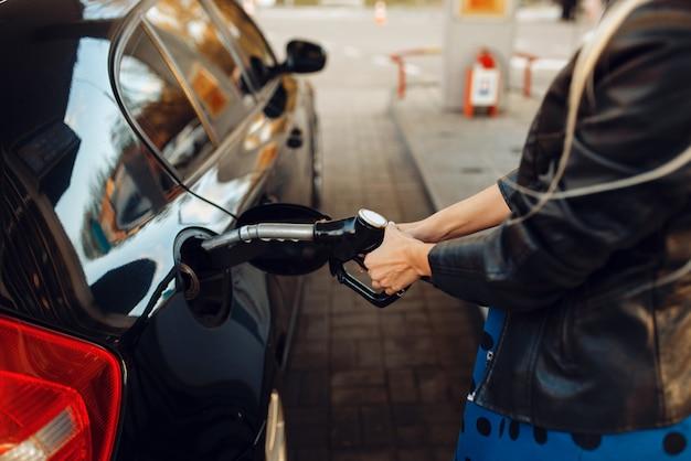 Donna con carburante per armi veicolo sulla stazione di servizio