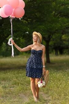 Donna con cesto di vimini, cappello, palloncini rosa e fiori