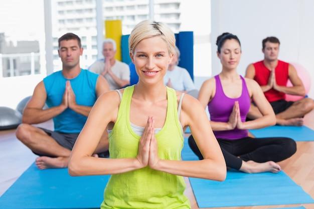 Donna con classe meditando in sala fitness