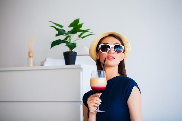 Donna con cocktail di benvenuto in camera d'albergo in vacanza