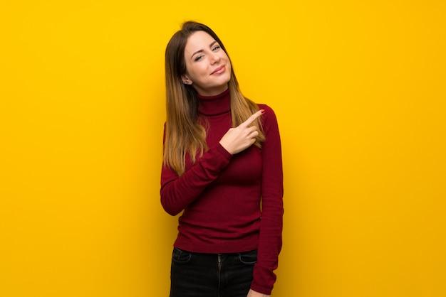 Donna con collo alto sopra la parete gialla che punta verso il lato per presentare un prodotto
