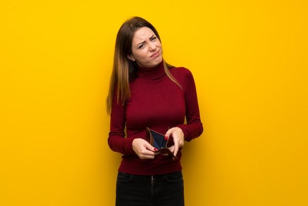 Donna con collo alto sopra la parete gialla che tiene un portafoglio
