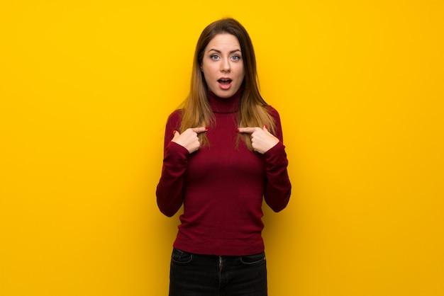 Donna con collo alto sul muro giallo con espressione facciale a sorpresa