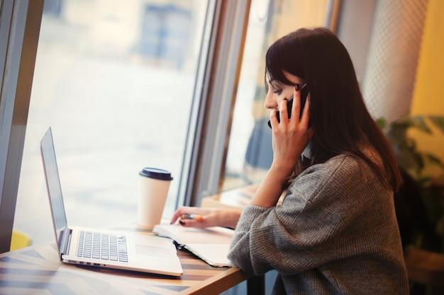Donna con computer portatile e telefono cellulare che lavora in un caffè