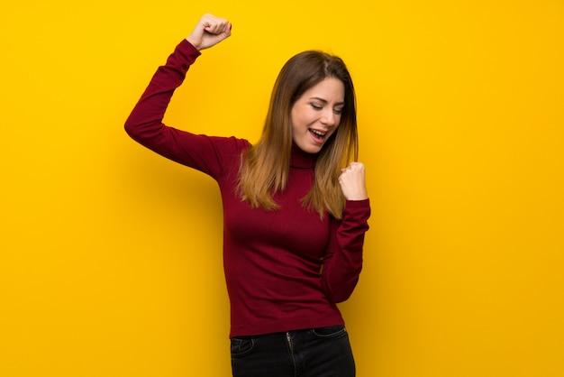 Donna con dolcevita sul muro giallo che celebra una vittoria