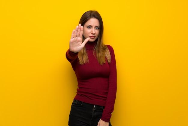 Donna con dolcevita sul muro giallo che ferma il gesto negando una situazione che pensa che sia sbagliato
