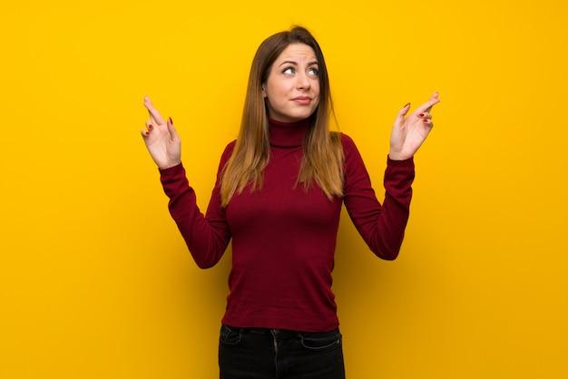 Donna con dolcevita sul muro giallo con le dita che attraversano e che desiderano il meglio