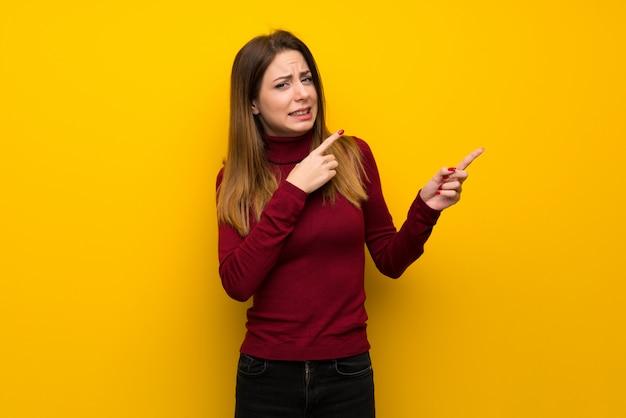 Donna con dolcevita sul muro giallo spaventato e che punta verso il lato
