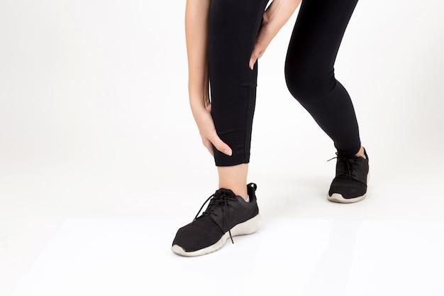 Donna con dolore alle gambe. lo studio ha sparato su priorità bassa bianca. concetto di fitness e salute