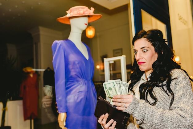Donna con espressione di delusione per non avere soldi per comprare abiti alla moda.