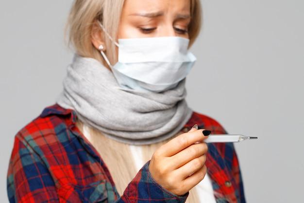 Donna con febbre che guarda e che controlla la sua temperatura