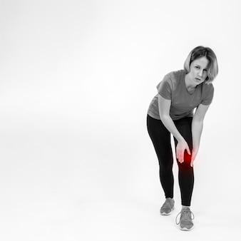 Donna con ginocchio dolorante