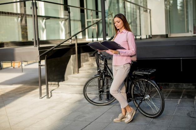 Donna con gli archivi nelle mani che stanno all'aperto davanti alla bici elettrica