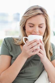Donna, con gli occhi chiusi che odoravano la bevanda nella sua tazza, tenuta fino al naso