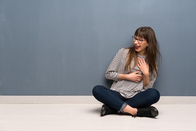 Donna con gli occhiali che si siedono sul pavimento che sorride molto