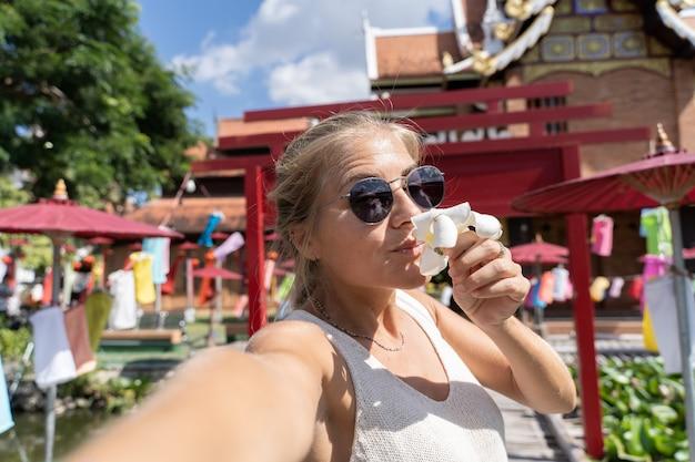 Donna con gli occhiali da sole che fa un selfie odorando un giglio bianco