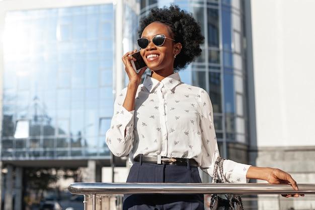 Donna con gli occhiali da sole che parla sopra il telefono