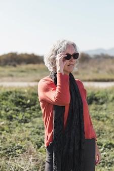 Donna con gli occhiali da sole che passa tempo all'aperto