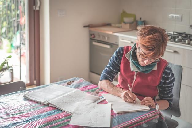 Donna con gli occhiali seduto al tavolo