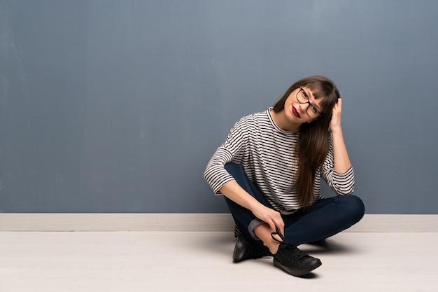 Donna con gli occhiali seduto sul pavimento con gli occhiali e sorridente