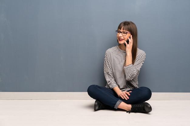 Donna con gli occhiali seduto sul pavimento mantenendo una conversazione con il telefono cellulare