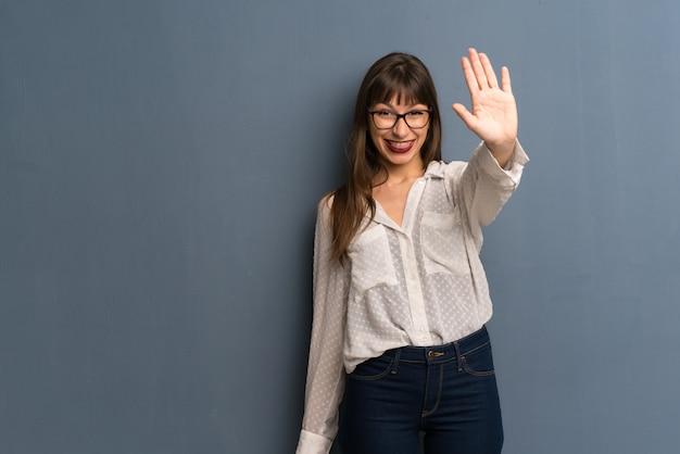 Donna con gli occhiali sul muro blu salutando con la mano con l'espressione felice