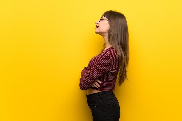 Donna con gli occhiali sul muro giallo in posizione laterale