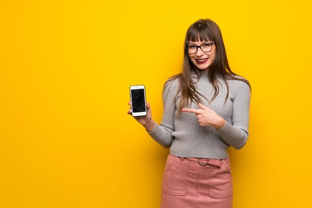 Donna con gli occhiali sulla parete gialla felice e indicando il cellulare