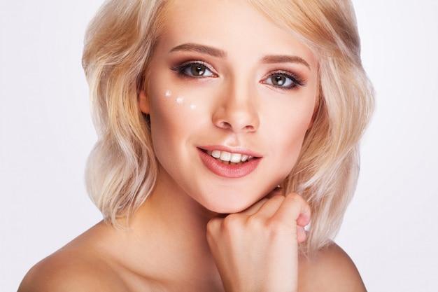 Donna con gocce di crema cosmetica sotto gli occhi