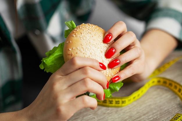 Donna con hamburger e nastro di misurazione durante la dieta