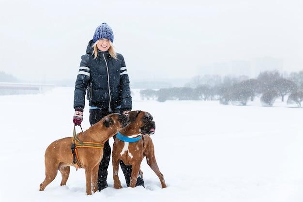 Donna con i cani del pugile un giorno di inverno nevoso su una passeggiata