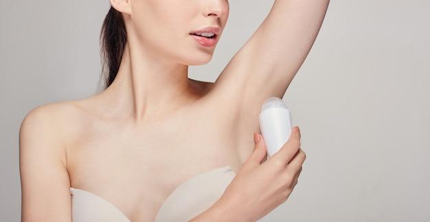 Donna con i capelli castani con pelle fresca e pulita in posa sul grigio con deodorante in mano, guardando dritto e sorridente con i denti bianchi