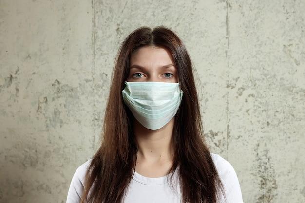 Donna con i capelli castani e una mascherina medica per l'influenza del protettore