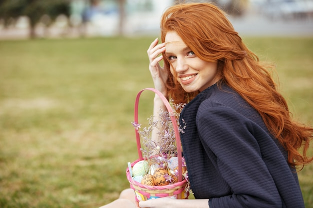 Donna con i capelli lunghi, tenendo il cestino da picnic di pasqua