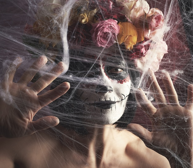 Donna con i capelli neri è vestita da una ghirlanda di rose multicolori e il trucco è fatto sul suo viso cranio di zucchero per il giorno dei morti