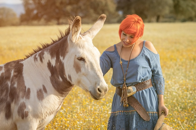 Donna con i capelli rossi vicino a un asino